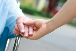 A person holding the hand of a senior citizen receiving home care services administered by Seniors Helping Seniors - Bucks Country in Warminster, PA