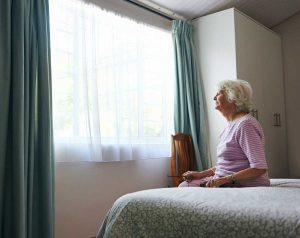 A senior citizen sitting on her bed while she is under 24-hour care from Seniors Helping Seniors - Bucks County in Warminster, PA